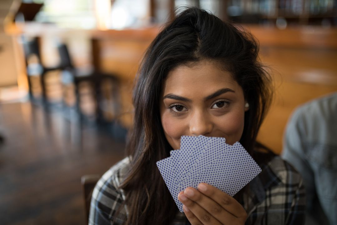 Portrait of smiling beautiful woman holding cards in bar Free Stock Images from PikWizard