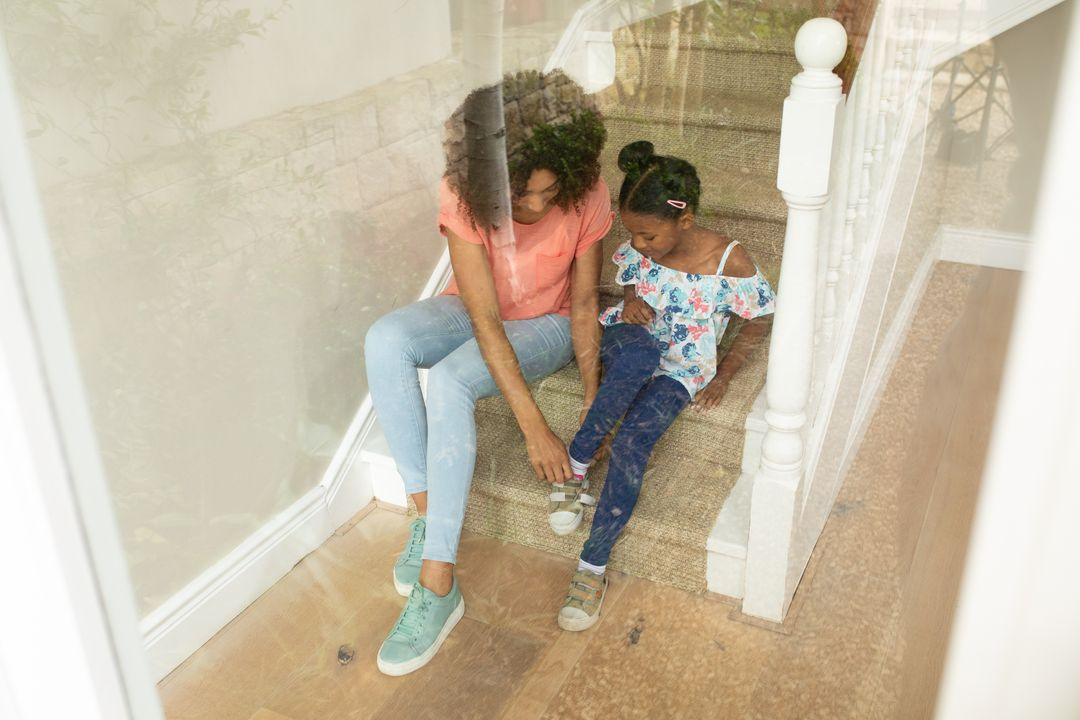 African American woman enjoying her time at home with her daughter, sitting on staircase mother helping daughter putting her shoes on. Family togetherness domestic life. Free Stock Images from PikWizard