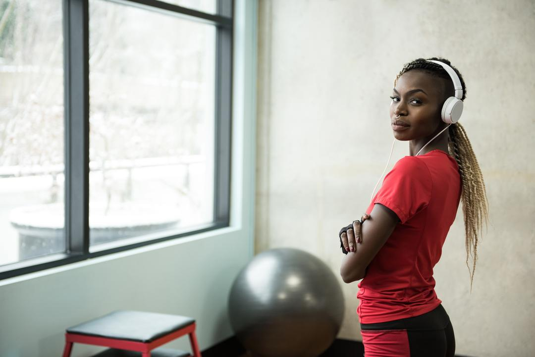 Portrait of fit woman standing with arms crossed in the gym