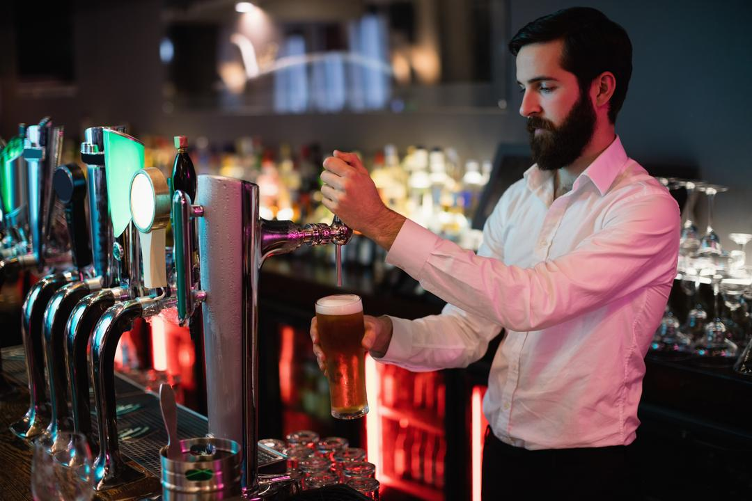 Bartender filling beer from bar pump at bar counter