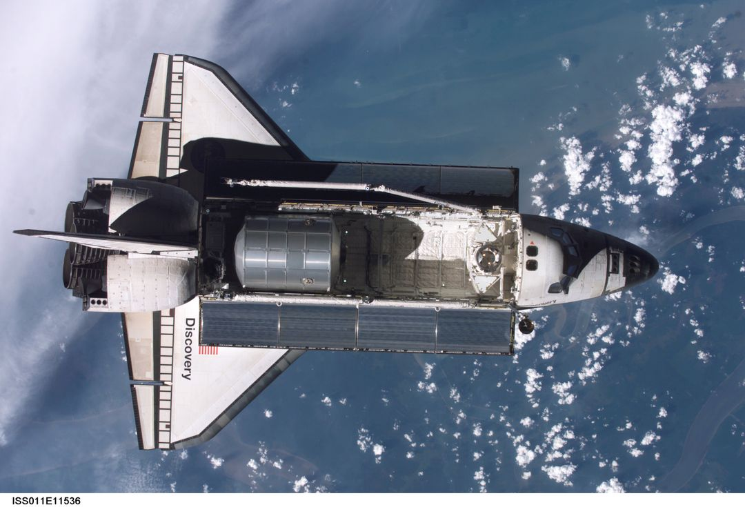 Launched on July 26 2005 from the Kennedy Space Center in Florida, STS-114 was classified as Logistics Flight 1. Among the Station-related activities of the mission were the delivery of new supplies and the replacement of one of the orbital outpost's Control Moment Gyroscopes (CMGs). STS-114 also carried the Raffaello Multi-Purpose Logistics Module (MPLM) and the External Stowage Platform-2.  Back dropped by popcorn-like clouds, the MPLM can be seen in the cargo bay as Discovery undergoes rendezvous and docking operations. Cosmonaut Sergei K. Kriklev, Expedition 11 Commander, and John L. Phillips, NASA Space Station officer and flight engineer photographed the spacecraft from the International Space Station (ISS).