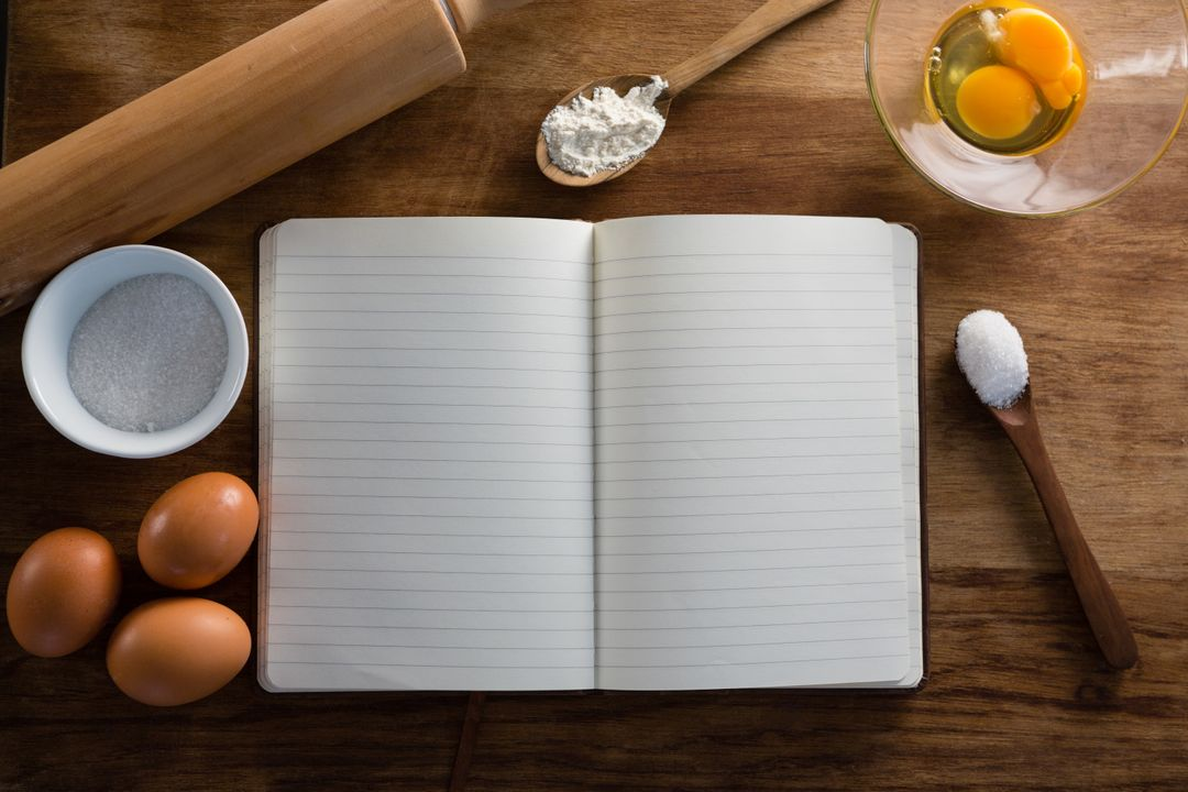 Over head view of book, eggs, flour, spoon and rolling pin kept on a table Free Stock Images from PikWizard