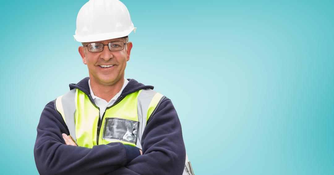 Portrait of architect in hardhat and spectacles standing with arms crossed against blue background