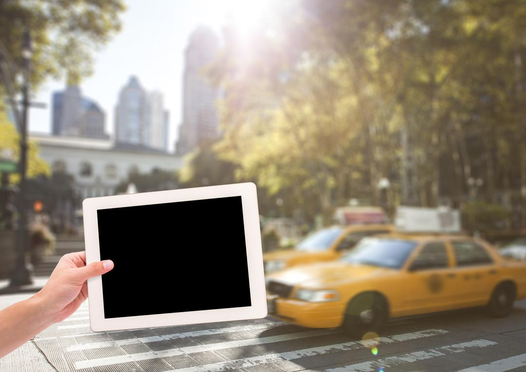 Digital composite of hand with tablet in front of taxis