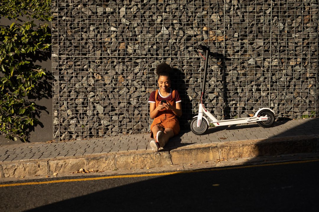 Front view of a happy mixed race woman enjoying free time in a city on a sunny day, sitting on pavement, using smartphone, an electric scooter next to her. Free Stock Images from PikWizard
