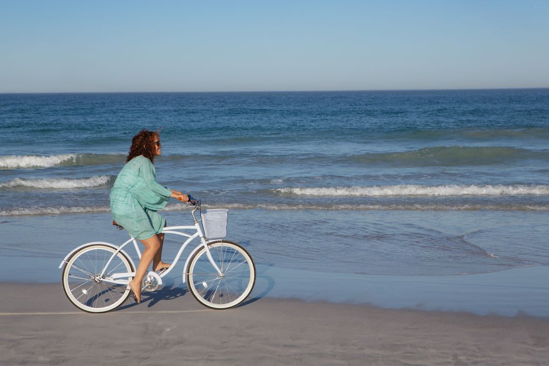 Side view of mixed race woman riding bicycle on beach in the sunshine