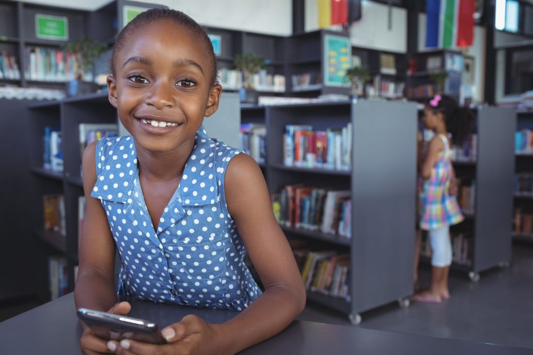 Portrait of smiling girl with mobile phone at desk in library Free Stock Images from PikWizard