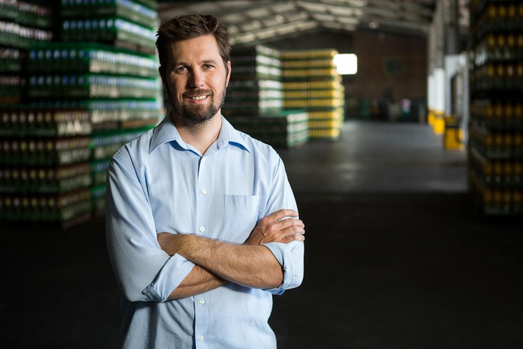 Portrait of confident male worker standing in warehouse Free Stock Images from PikWizard