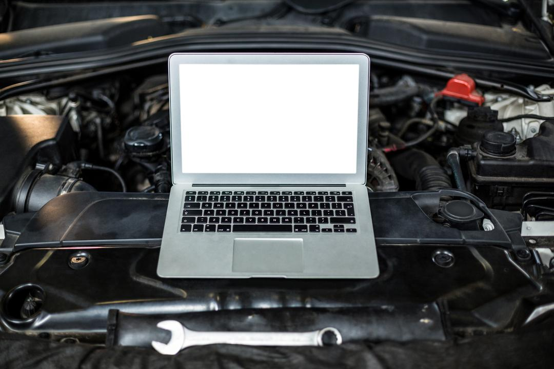 Laptop on a car engine in repair garage