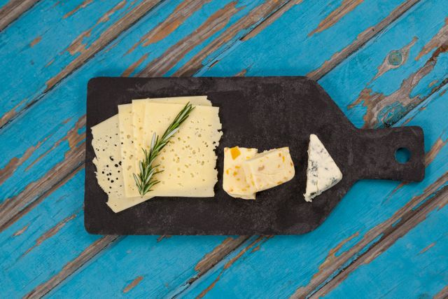 Cheese with rosemary on chopping board