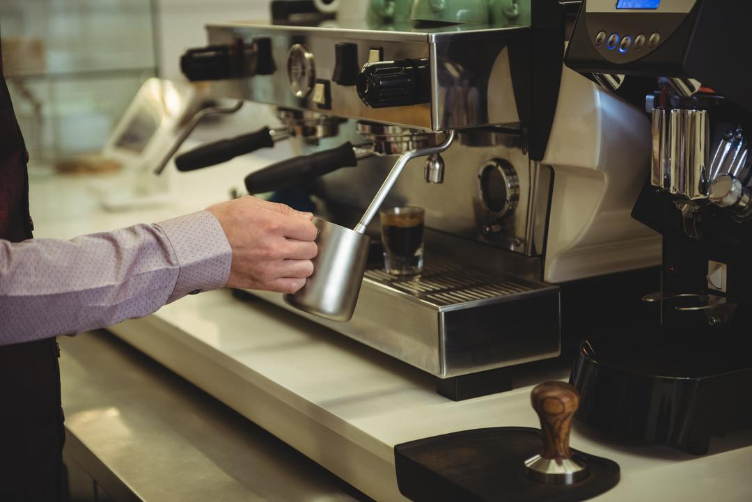 Mid section of man preparing coffee in the coffee shop