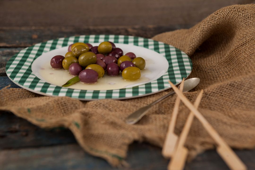 Close up of green and black olives served in plate on wooden table