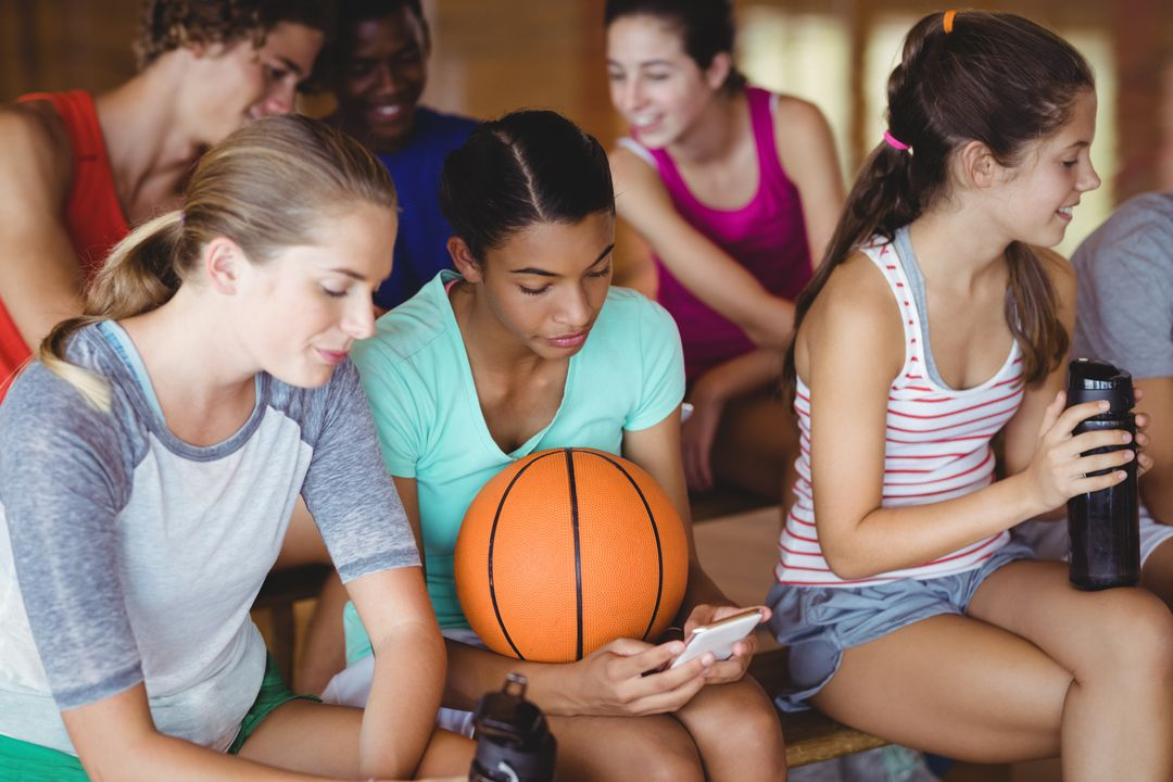 Smiling high school kids using mobile phone while relaxing in basketball court Free Stock Images from PikWizard