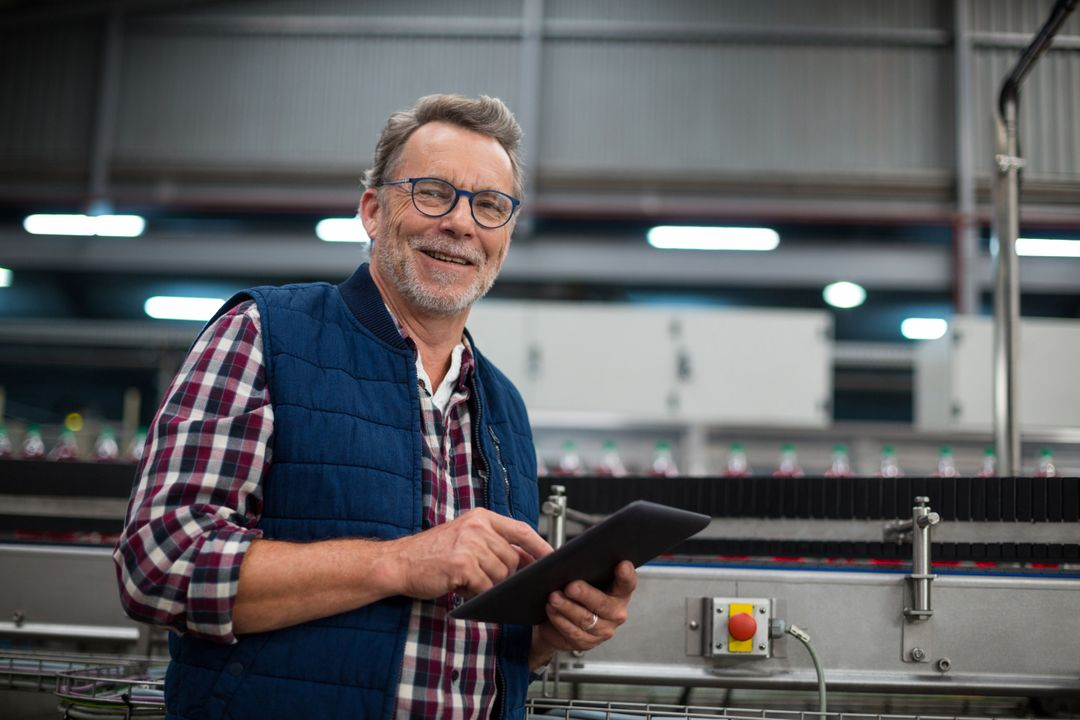 Portrait of smiling factory worker using digital tablet in the factory
