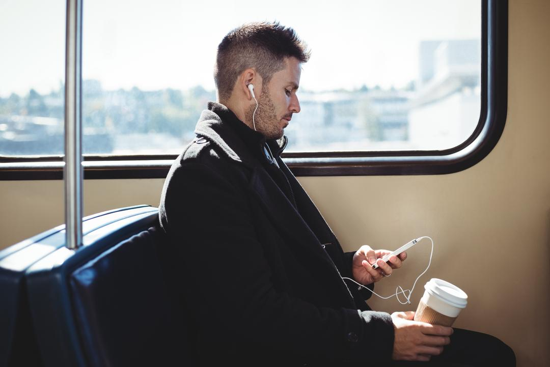 Businessman holding a disposable coffee cup and listening to music on mobile phone in the train