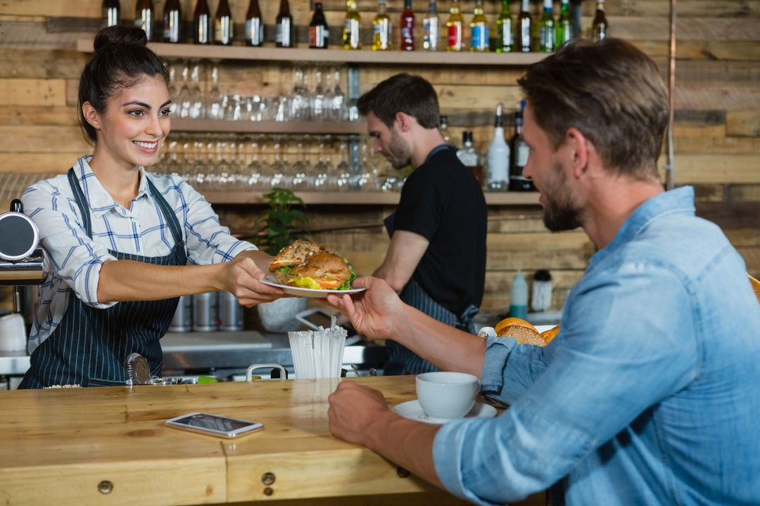 Waitress serving breakfast to man at counter in cafe