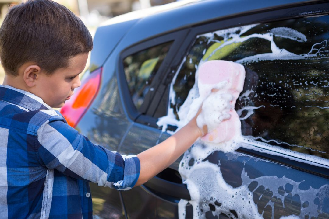 Teenage boy washing a car on a sunny day Free Stock Images from PikWizard