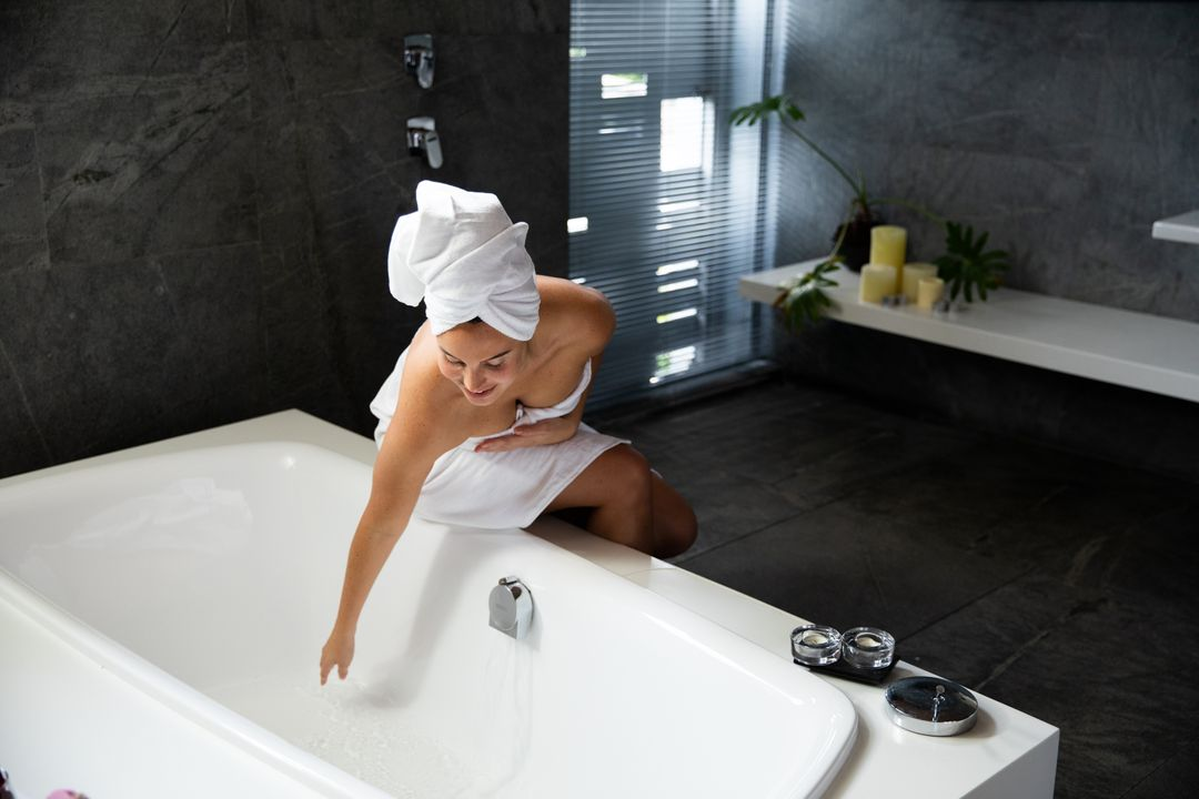 Front view of a Caucasian woman wearing a bath towel and with her hair wrapped in a towel, sitting on the edge of the bath and touching the water in a modern bathroom Free Stock Images from PikWizard