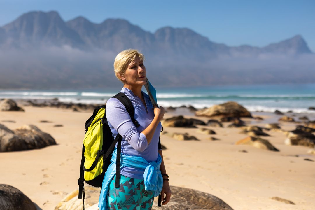 Caucasian hiker senior woman with backpack removing face mask while standing on the beach. Trekking hiking and adventure during coronavirus pandemic concept. Free Stock Images from PikWizard