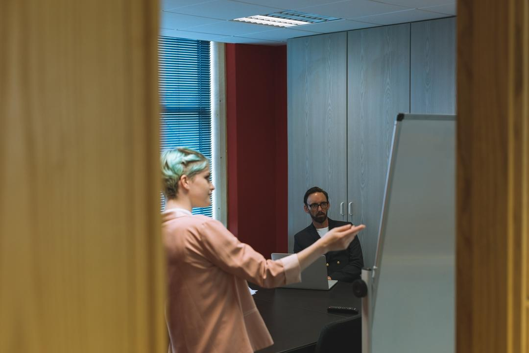 Executives discussing over flip chart in conference room