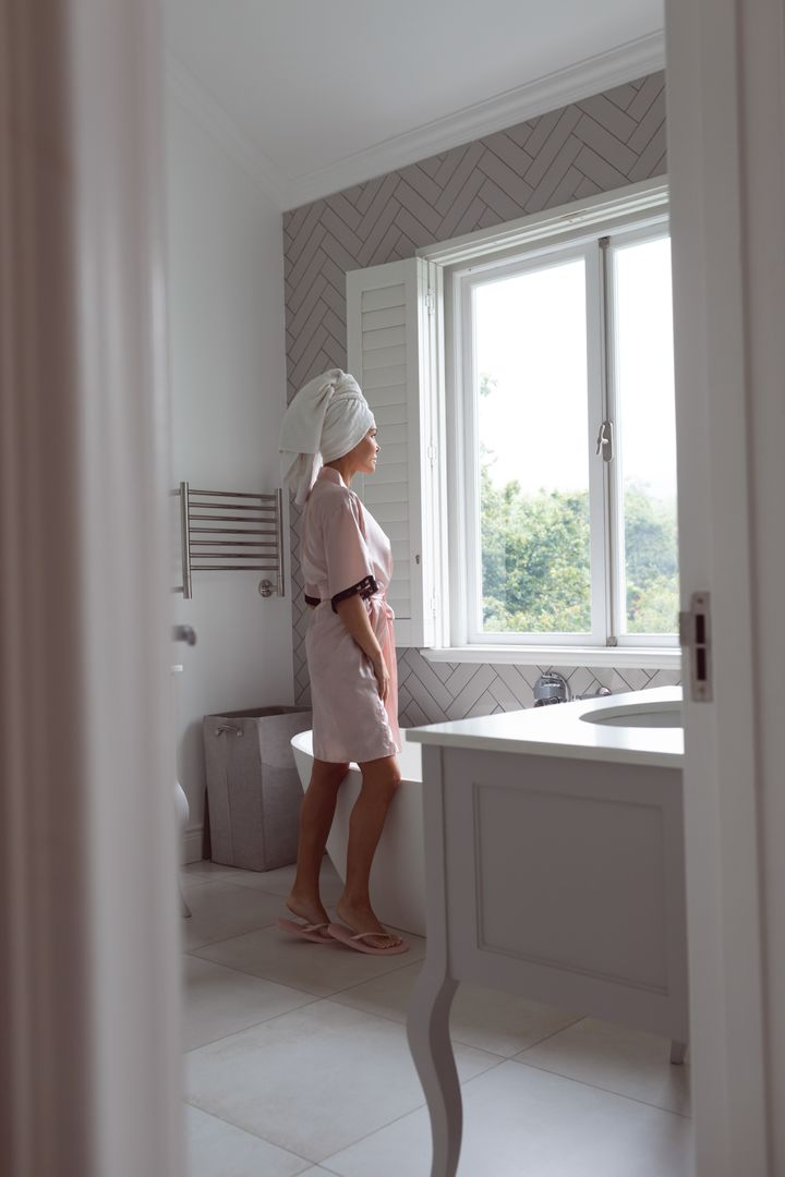 Beautiful woman standing while looking outside the window in bathroom at home