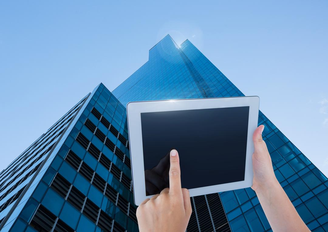 Digital composite of Holding tablet with skyscraper background