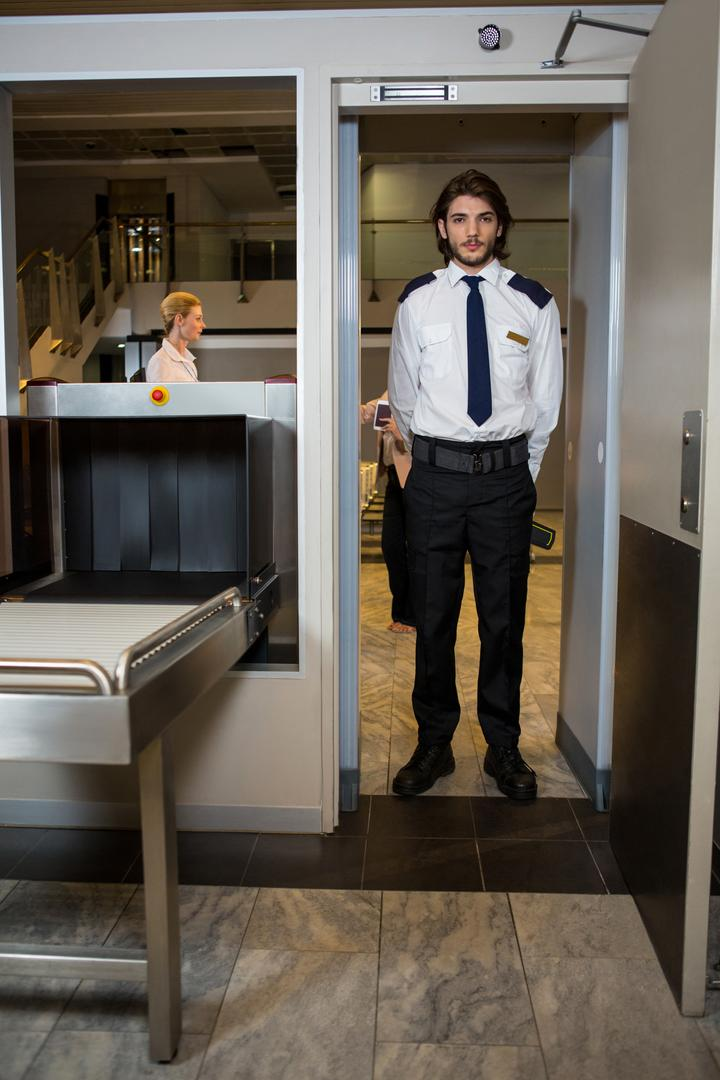 Security guard standing under the scanning door in the airport terminal