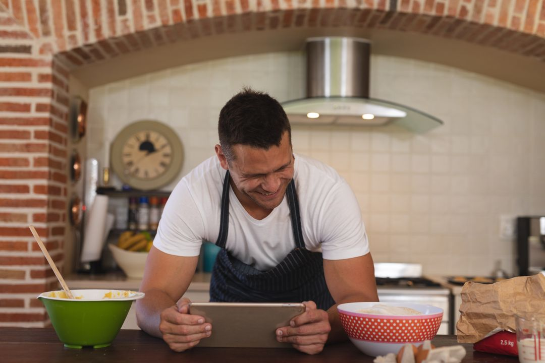 Front view of a caucasian man leaning on a kitchen table while holding a tablet with a grin on his face. Beside him are cooking ingredients. Free Stock Images from PikWizard