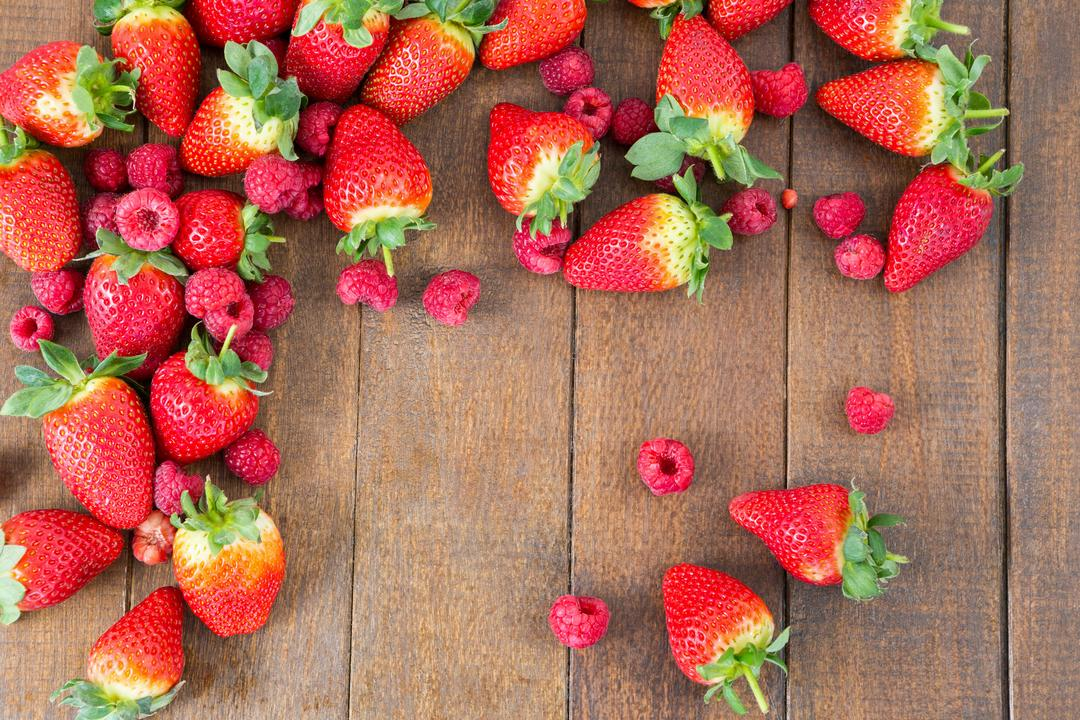 Fresh strawberries and raspberries arranged on wooden board
