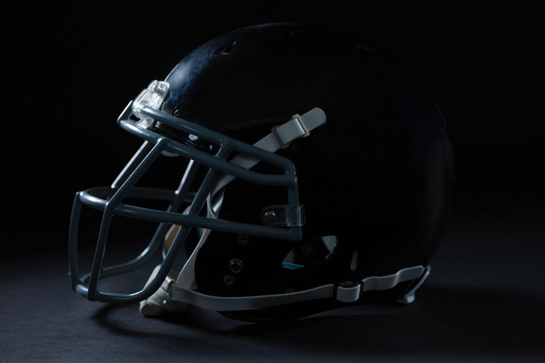 Close-up of American football head gear on a black background