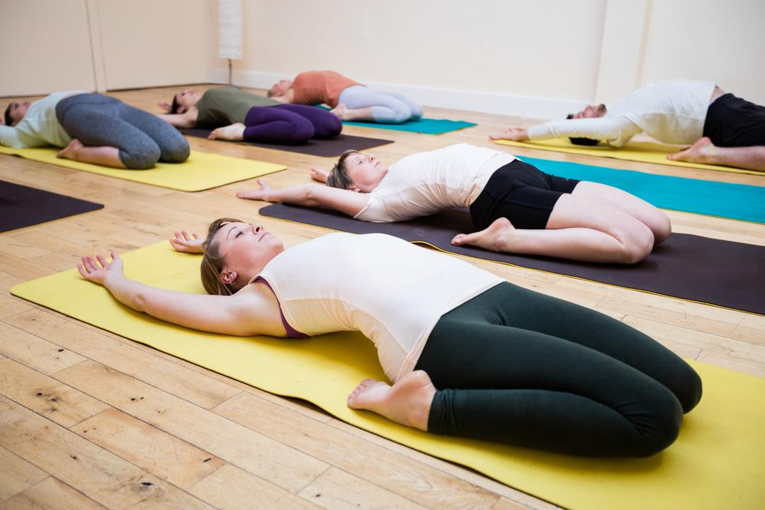 Group of people performing supta virasana on exercise mat in fitness studio