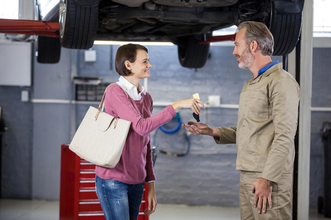 Customer giving her car keys to mechanic at the repair garage Free Stock Images from PikWizard