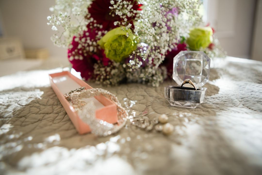 Image of wedding flowers with ring on lace tablecloth