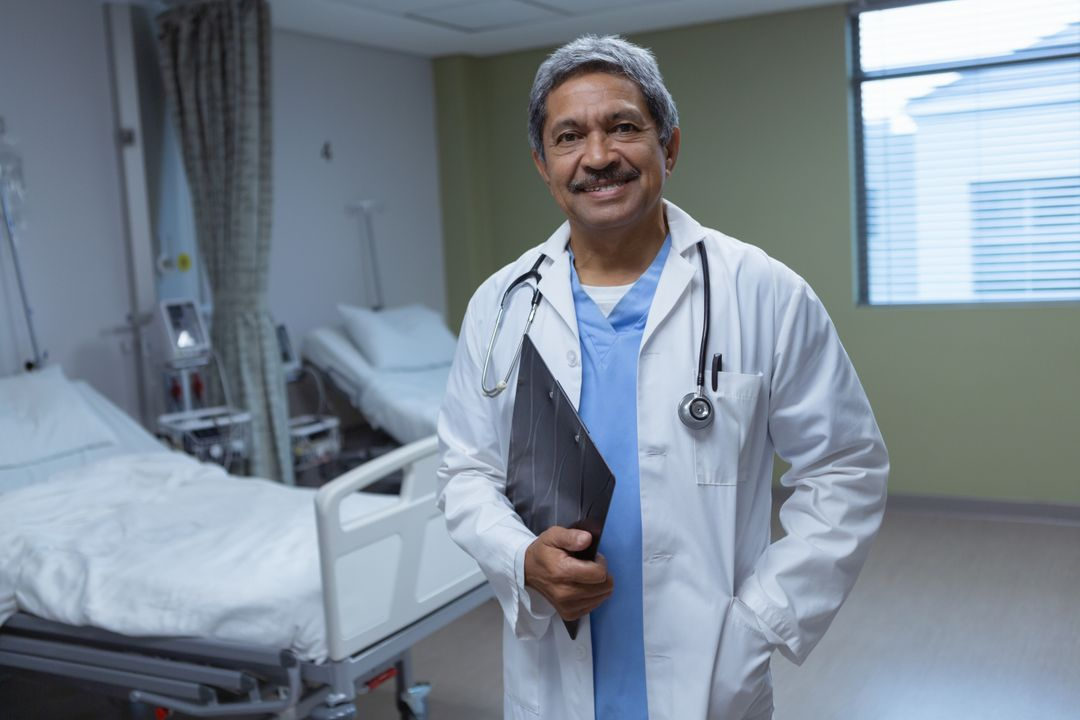 Front view of mature male doctor standing with clipboard in medical ward at hospital  Free Stock Images from PikWizard