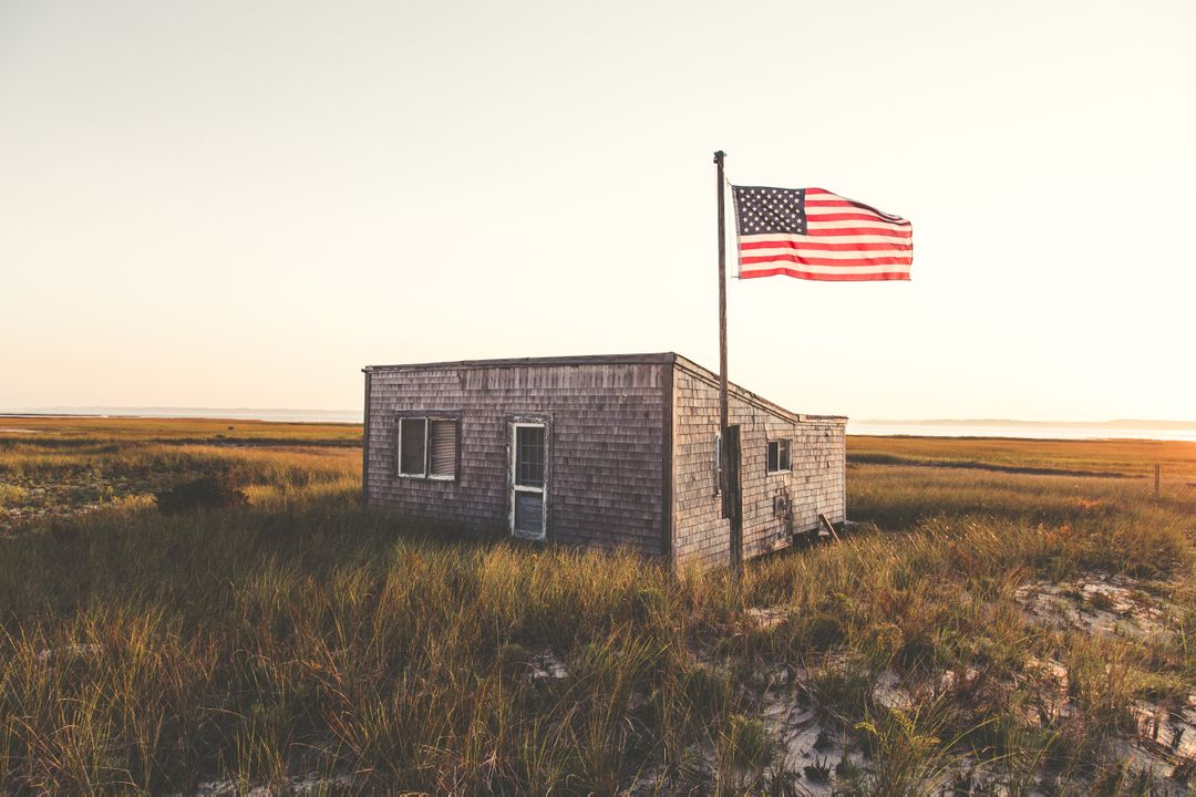 U.s Flag on Green Grassland in Front of Gray Concrete House