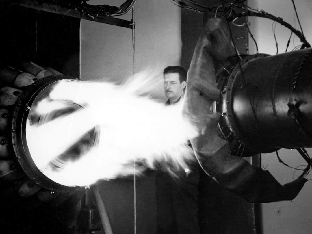 A mechanic watches the firing of a General Electric I-40 turbojet at the National Advisory Committee for Aeronautics (NACA) Lewis Flight Propulsion Laboratory. The military selected General Electric's West Lynn facility in 1941 to secretly replicate the centrifugal turbojet engine designed by British engineer Frank Whittle. General Electric's first attempt, the I-A, was fraught with problems. The design was improved somewhat with the subsequent I-16 engine.  It was not until the engine's next reincarnation as the I-40 in 1943 that General Electric's efforts paid off. The 4000-pound thrust I-40 was incorporated into the Lockheed Shooting Star airframe and successfully flown in June 1944. The Shooting Star became the US's first successful jet aircraft and the first US aircraft to reach 500 miles per hour.    NACA Lewis studied all of General Electric's centrifugal turbojet models during the 1940s. In 1945 the entire Shooting Star aircraft was investigated in the Altitude Wind Tunnel. Engine compressor performance and augmentation by water injection; comparison of different fuel blends in a single combustor; and air-cooled rotors were studied.   The mechanic in this photograph watches the firing of a full-scale I-40 in the Jet Propulsion Static Laboratory. The facility was quickly built in 1943 specifically in order to test the early General Electric turbojets. The I-A was secretly analyzed in the facility during the fall of 1943.