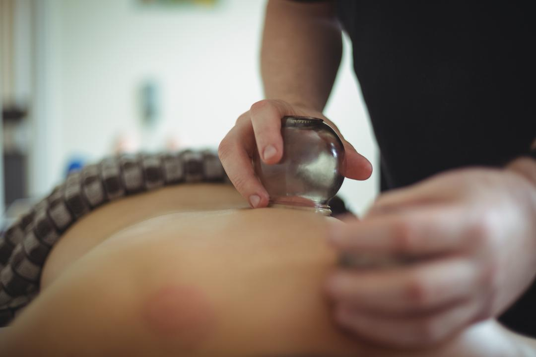 Mid section of therapist giving cupping therapy to man in spa