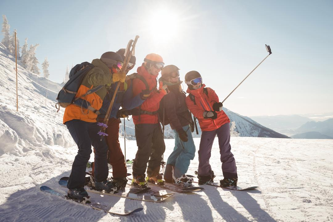 Group of skiers taking selfie on mobile phone during winter