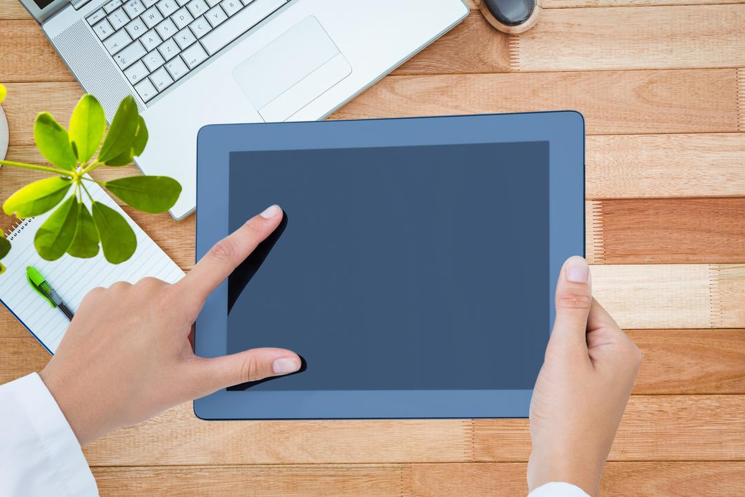Image of a Person Holding a Tablet and a Laptop on a Desk in the Background