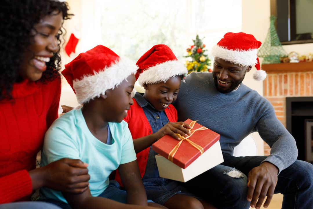 Close up of an african-american family wearing santa hats sitting on the couch and watching the daughter open her christmas present. Behind them is a christmas tree. Free Stock Images from PikWizard