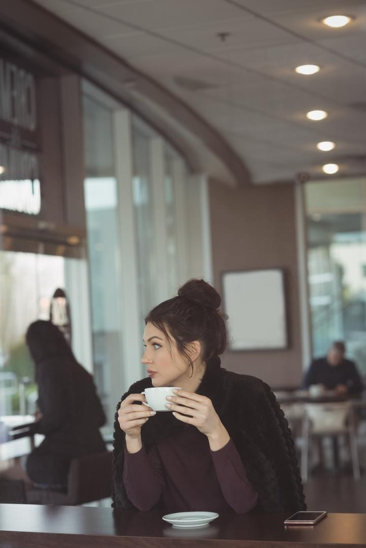 Thoughtful female executive having coffee in office cafeteria