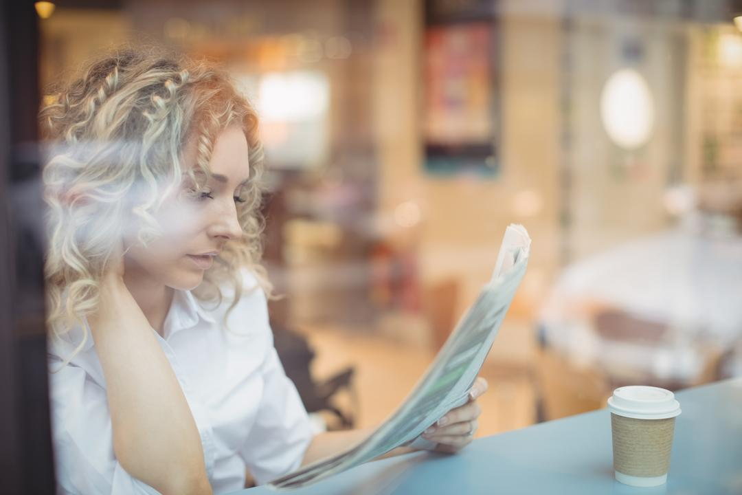 Woman reading newspaper at counter in cafeteria Free Stock Images from PikWizard