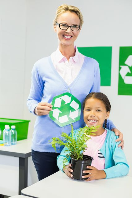 Teacher and schoolgirl with recycle logo in classroom at school