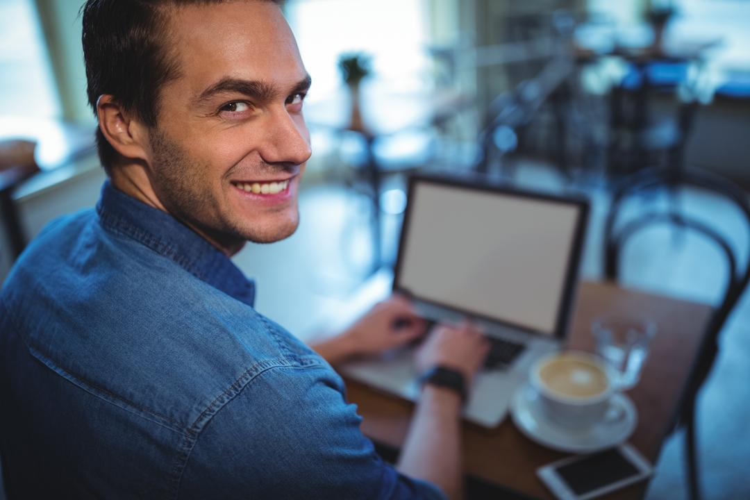 Portrait of man using laptop while having coffee in café Free Stock Images from PikWizard