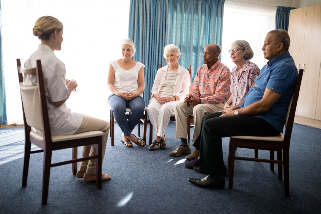 Female doctor sitting with senior people on chairs against window at retirement home