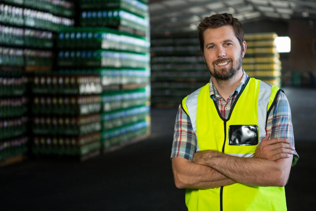 Portrait of confident male worker with arms crossed standing in warehouse