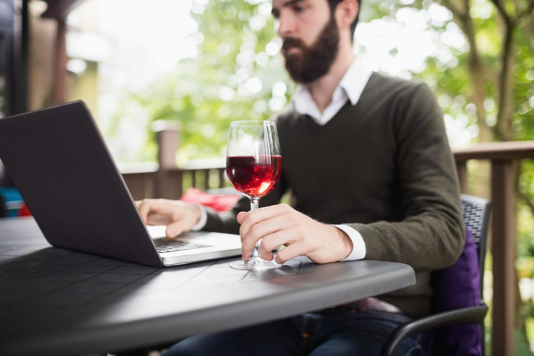 Man using laptop while having glass of wine in bar