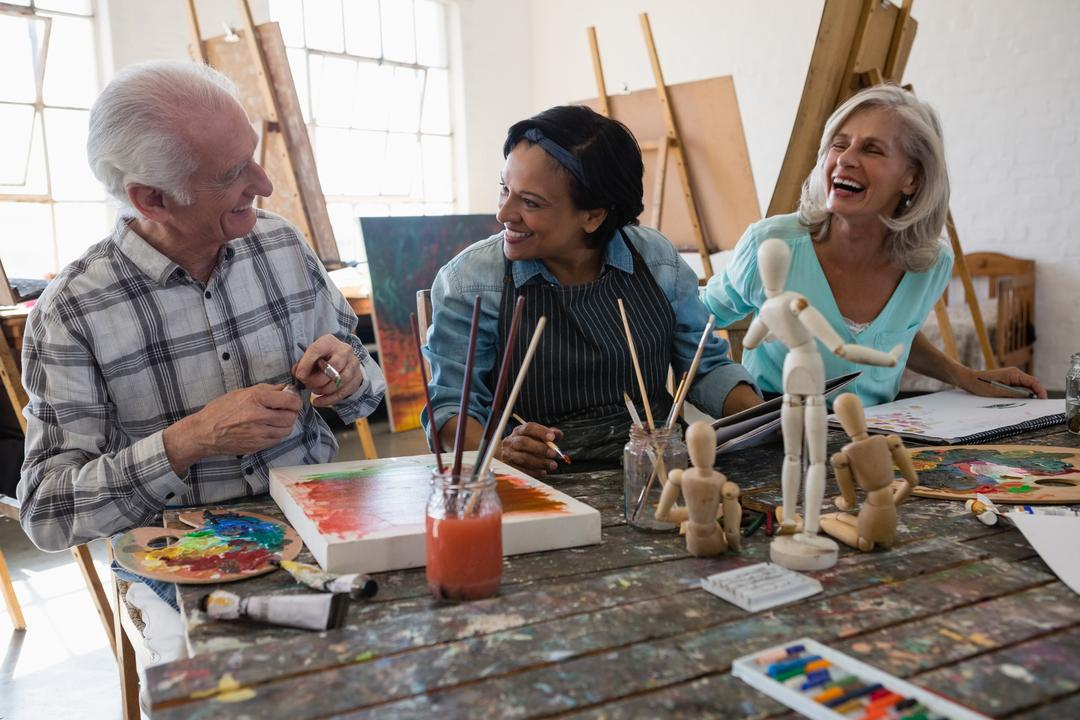 Cheerful senior male and female artists at table in art class