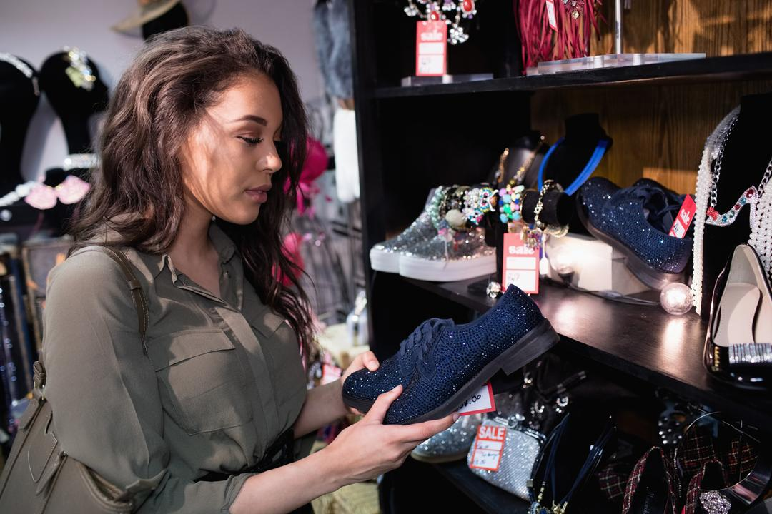 Woman selecting shoes in footwear section of boutique