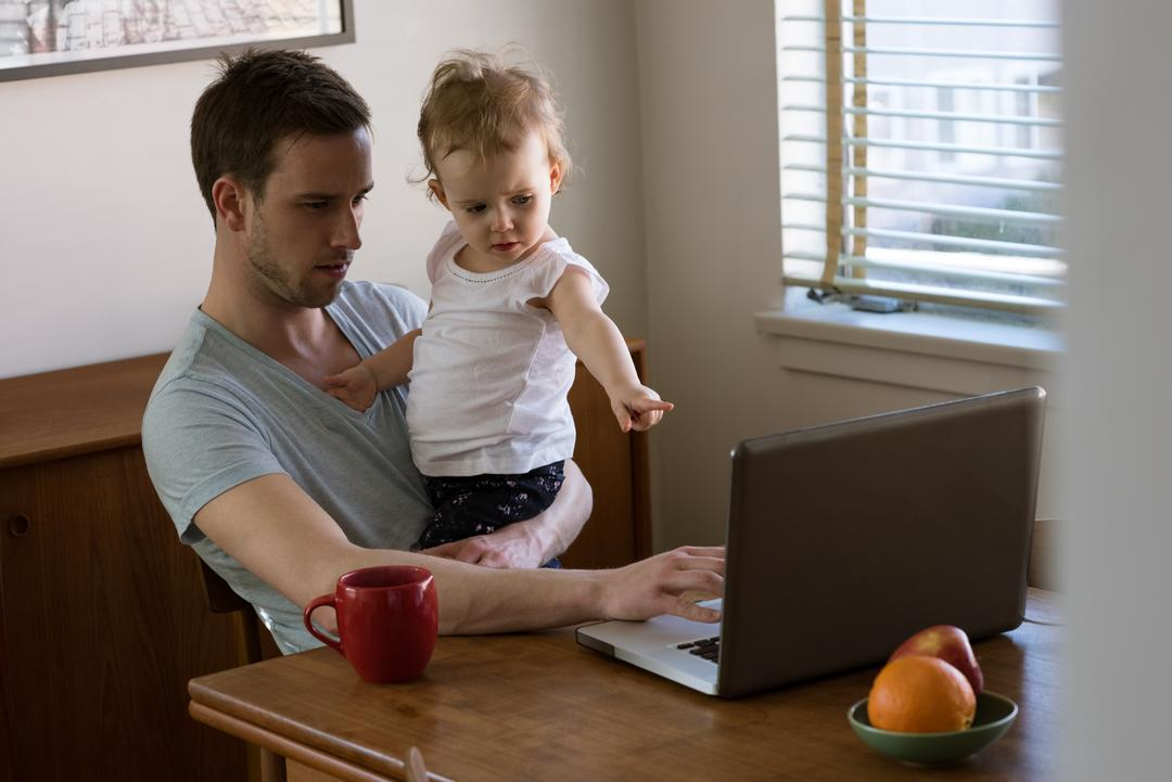 Daughter gesturing while father using laptop at table by window Free Stock Images from PikWizard
